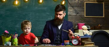 Art lesson concept. Teacher with beard, father teaches little son to draw in classroom, chalkboard on background. Child. And teacher on busy face painting stock photography