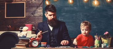 Art lesson concept. Teacher with beard, father teaches little son to draw in classroom, chalkboard on background. Child. And teacher on busy face painting royalty free stock photos