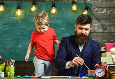 Art lesson concept. Teacher with beard, father teaches little son to draw in classroom, chalkboard on background. Child. Cheerful and teacher painting, drawing royalty free stock photos