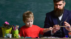 Art lesson concept. Teacher with beard, father teaches little son to draw in classroom, chalkboard on background. Talented artist spend time with son. Child stock photography