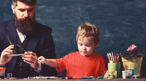 Art lesson concept. Teacher with beard, father teaches little son to draw in classroom, chalkboard on background. Talented artist spend time with son. Child royalty free stock images