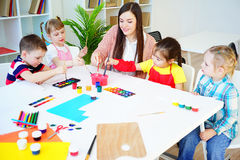 Art lesson in kindergarten. Kids painting on an art class at school stock images