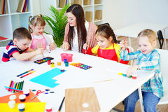 Art lesson in kindergarten. Kids painting on an art class at school royalty free stock photography