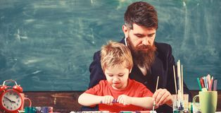 Art lesson at kindergarten. Teacher helping the boy to create picture. Man painting with long brush while kid opens the royalty free stock image