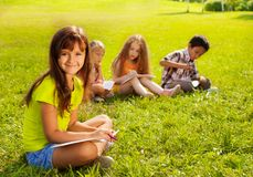Art lesson outside. Group of boys and girls painting sitting outside in the grass Royalty Free Stock Photo