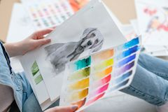 Art lifestyle drawing self expression picture. Creative art lifestyle. drawing hobby and self expression. woman looking at picture of a dog and color swatches stock photography