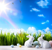 Art Little Easter bunny and Easter eggs on green grass Stock Image