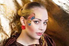 Art make up. Creative makeup, new crazy conceptual idea, party banner. golden red bold body art painting. Crazy new graphic abstract picture on woman face. shiny Royalty Free Stock Photo