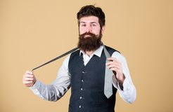 Art of manliness. Man bearded hipster try to make knot. Different ways of tying necktie knots. How to tie necktie. How. To tie simple knot. Start with your stock image