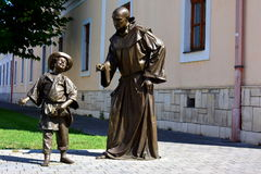 Art Metal. Metal man, a monk and a boy, concept Metal people pictures of Romania, the emotions of the body, against the walls of the church, smiling boy, trip Stock Photos