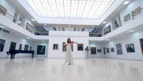 Art museum with a female violinist playing the instrument. 4K stock footage