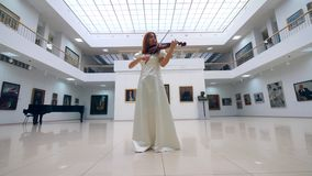 Art museum and a lovely lady playing the violin stock video footage
