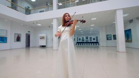 Art museum with a woman in a white dress playing the violin. 4K stock video