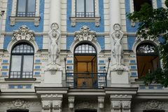 Art Nouveau style architecture on an old building. Art Nouveau style architecture on a historic building with statues of young maidens holding aloft wreaths on Royalty Free Stock Photo