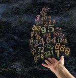 The Art of Numerology. Female hand palm up with a group of random gold transparent numbers floating up and away on a dark rustic stone effect background with stock photos