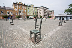 Art objects with iron chairs on cobblestone street erected Stock Photos