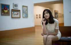 Art. One woman sitting on a bench and looking art gallery Stock Photography