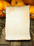Art orange pumpkins and paper on wooden background Stock Images