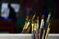 Art paint brushes in cup are located in the children's entertain. Ment hall at the mirror stock photos