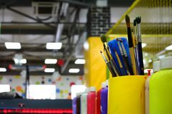 Art paint brushes in cup are located in the children's entertain. Ment hall royalty free stock photography