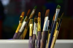 Art paint brushes in cup are located in the children's entertain. Ment hall at the mirror royalty free stock photography
