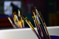 Art paint brushes in cup are located in the children's entertain. Ment hall at the mirror stock photography