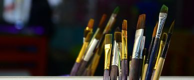 Art paint brushes in cup are located in the children's entertain. Ment hall at the mirror royalty free stock images