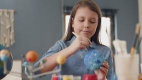 Art Painting do globo da terra pela criança criativa em casa para o conceito do passatempo filme