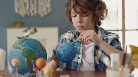 Art Painting of Earth Globe by Creative Child at Home for Hobby Concept. Painting of Blue Ball by Small Man. Paintbrush in Hand of Sitting School Pupil stock video footage