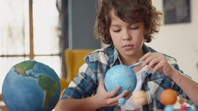 Art Painting of Earth Globe by Creative Children at School for Education Concept. Painting of Blue Ball by Small Man. Paintbrush in Hand of Sitting School Pupil stock footage