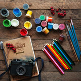 Art of Painting. Paint buckets on wood background. Different paint colors painting on wooden background. Painting set: brushes, pa Royalty Free Stock Photos