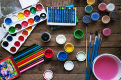 Art of Painting. Paint buckets on wood background. Different paint colors painting on wooden background. Painting set: brushes, pa