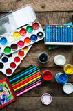 Art of Painting. Paint buckets on wood background. Different paint colors painting on wooden background. Painting set: brushes, pa Stock Photo