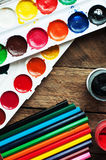 Art of Painting. Paint buckets on wood background. Different paint colors painting on wooden background. Painting set: brushes, pa Royalty Free Stock Photo