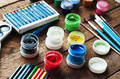 Art of Painting. Paint buckets on wood background. Different paint colors painting on wooden background. Painting set: brushes, pa Stock Image
