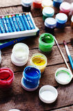 Art of Painting. Paint buckets on wood background. Different paint colors painting on wooden background. Painting set: brushes, pa Stock Photography