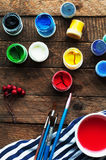 Art of Painting. Paint buckets on wood background. Different paint colors painting on wooden background. Painting set: brushes, pa Royalty Free Stock Images