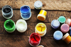 Art of Painting. Paint buckets on wood background. Different paint colors painting on wooden background. Painting set: brushes, pa Stock Photos