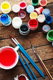 Art of Painting. Paint buckets on wood background. Different paint colors painting on wooden background. Painting set: brushes, pa Royalty Free Stock Photography
