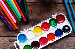 Art of Painting. Paint buckets on wood background. Different paint colors painting on wooden background. Painting set: brushes, pa Stock Images