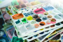 Art palette with blobs of paint and a brush in can Royalty Free Stock Image