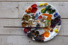 Art palette and brush with lots of colors, tempera and oil paint royalty free stock photography