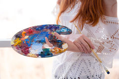 Art palette with oil paints and brush holded by woman Stock Photo