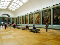 Art Interior Louvre Museum. Art patrons looks at painting hanging on the wall of the historic Louvre Museum stock images