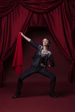 Art photo of fashion young woman on stage with red curtains. Royalty Free Stock Photo