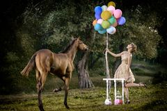 Beautiful girl with brown curly hair in wonderful dress ute posing smiling with colorful balloons and horse in fairytale forest royalty free stock images