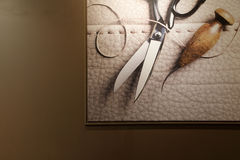 Art photo of scissors, leather and thread in photo frame on wall Stock Photo