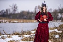 Art Photography Ideas Mystisk felik prinsessa i röd klänning och svart krona som läser den gamla boken Posera i Forest Outdoors royaltyfria foton