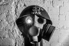Art picture of a military gas mask. On a white brick wall with shadows the inscription make photo not war on Fatherland defender day stock images