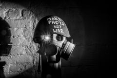 Art picture of a military gas mask. On a white brick wall with shadows the inscription make photo not war on Fatherland defender day stock image